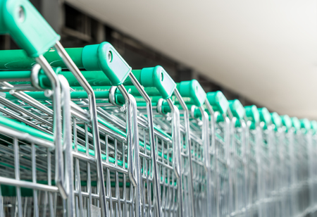 Row of Supermarket green emtal shopping cart Imagens
