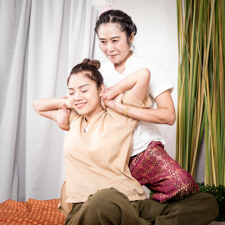 Happy woman is getting thai massage stretching position