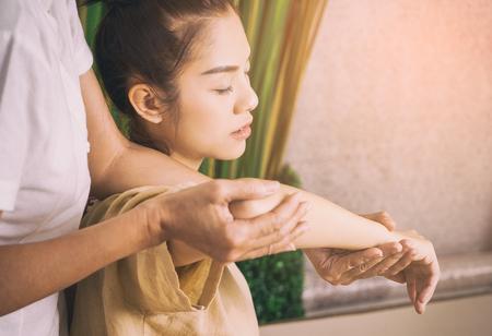 태국 안마사는 여자 팔 마사지를하고있다.