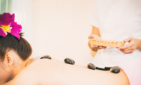 Hot stones placed on a women back in Beauty Spa