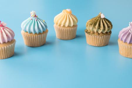 Colorful pastel cupcake line up on blue copy space Banco de Imagens