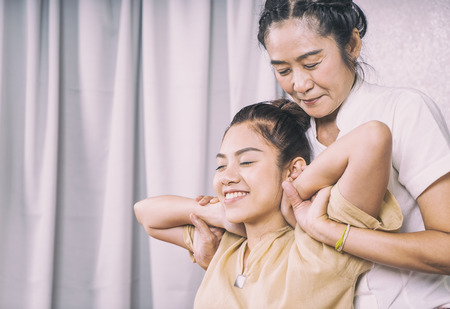 Thai Therapist is stretching a woman shoulder and neck