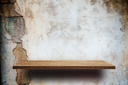 Empty wooden shelves display on cracked brick wall Фото со стока