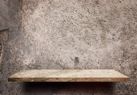 Empty display shelf on grungy dirt cement wall for product display