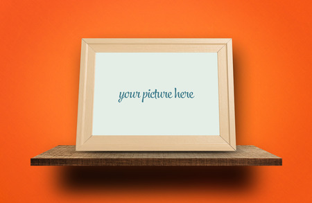 Empty photo frame on wooden shelves on orange wall