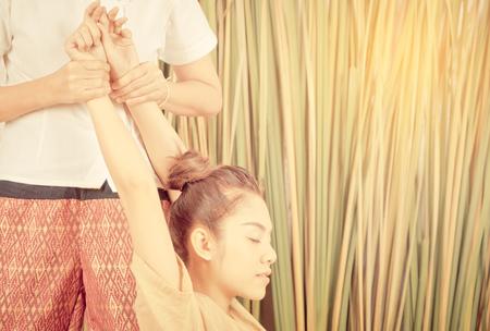 Vrouw met wapen in de Thaise positie van de massagerek Stockfoto