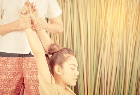 Woman with arm in thai massage stretch position Stock Photo