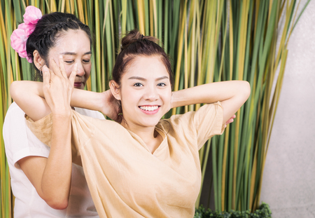 Woman is smiling while taking Thai massage therapy Stock Photo