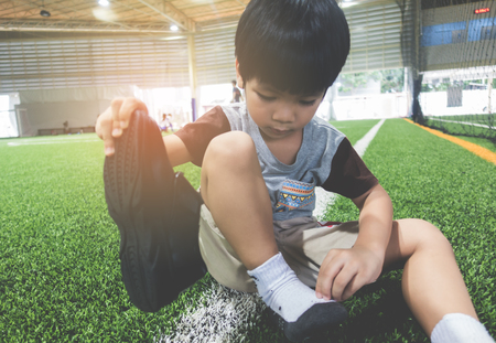 Boy taking shoes off getting ready for soccer training ground