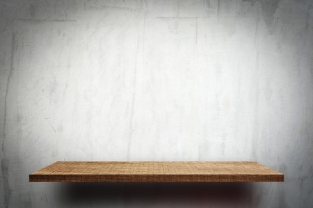 Blank wooden display shelf on white cement wall Stock Photo