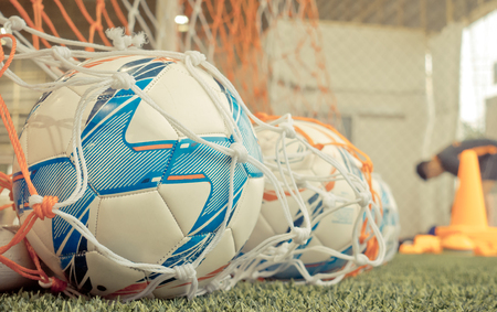 Soccer ball in football goal net in soccer training ground