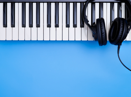 Music headphone on Music keyboard on blue copy space for Music concept Stock Photo
