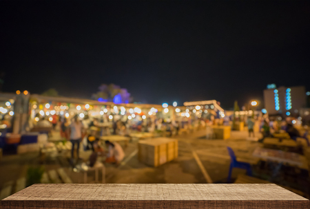 Empty wooden counter with Night street market background