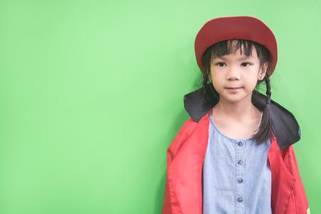 Kleines Mädchen im roten Pelzmantel auf grünem Hintergrund Standard-Bild - 93006710