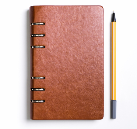 Leather cover notebook with a yellow pen on white background Imagens