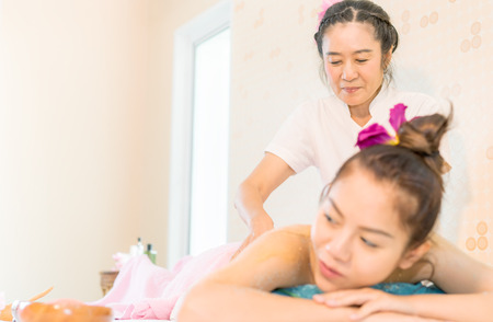 Thai Spa Therapist is giving a woman back massage Stock Photo