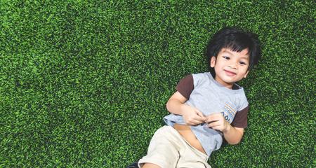Happy boy is lying on artifact grass field top view Banco de Imagens
