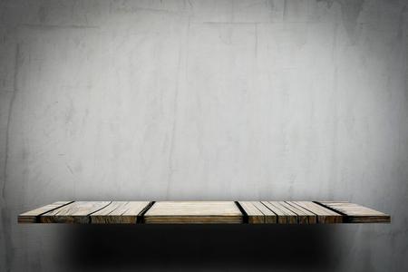 Empty wooden shelf display on gray wall