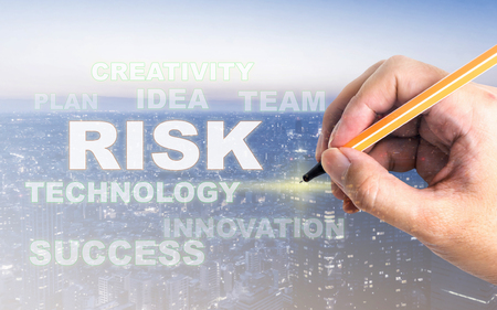 Hand writting on Risk on modern city light for business concept