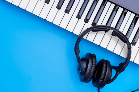 Music keyboard and Music headphone on blue copy space