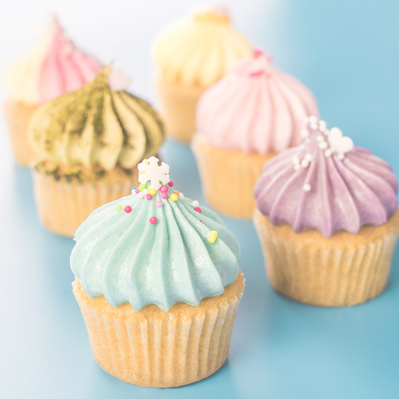 mini fancy cupcakes muffins on bright blue background Stock Photo