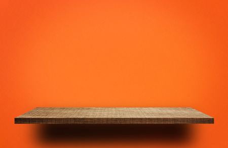 Empty wooden shelf on orange background for product display