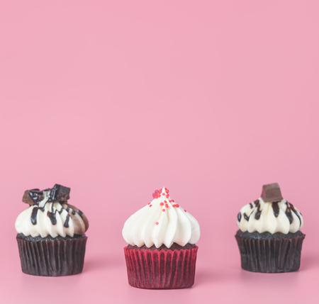 Three mini chocolate cupcake muffins on pink copy space Imagens