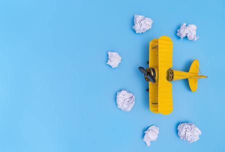 Het gele stuk speelgoed van het metaalvliegtuig op de blauwe ruimte van het hemelexemplaar Stockfoto