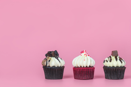 Three mini chocolate cupcakes on pink copy space