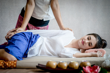 Woman is relaxing in thai Spa while massuer is massaging her arm Stock Photo
