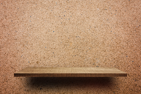 Empty wooden shelf on brown rock wall for product display