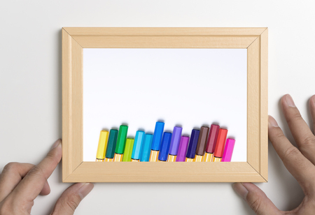 Hand holding frame mock up with color pencil for Art concept