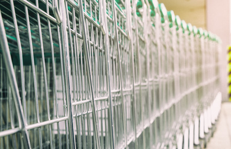 Metal shopping cart with green handle in a row