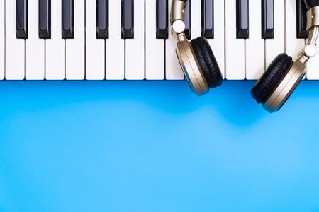 Muziektoetsenbord met gouden hoofdtelefoon voor blauwe exemplaar hieronder ruimte Stockfoto - 93155228