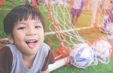 Happy Little boy behind the Goal in soccer training field