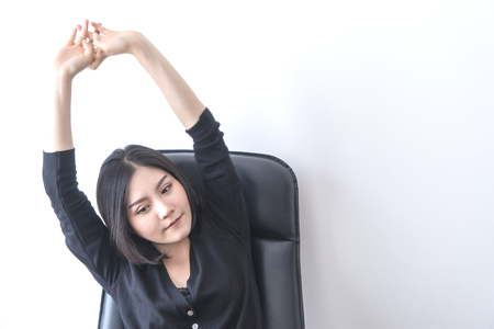 Female Asian office worker is stretching out after long hour of work Фото со стока