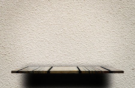 Wooden display shelf on Rough gray cement wall