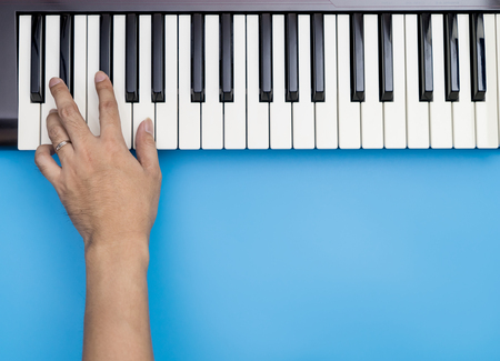 One hand playing keys on Music Keyboard with blue copy space