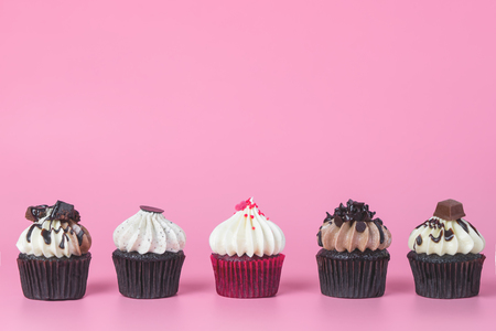 Five chocolate cupcake with red cupcake in the middle on pink background Stock Photo