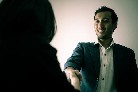 不誠実なビジネスマンは悪魔の表情でパートナーと握手をしています