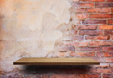Empty wooden display shelf on cracked brick wall Stock Photo
