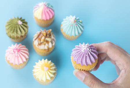 Hand holding purple cupcake with colorful cupcake on the background Stock Photo