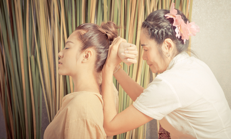 Thai Masseur is stretching a woman back arm in Thai massage spa
