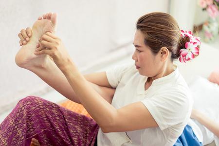 タイマッサージ師は、タイのマッサージスパで女性の足と足を伸ばしています
