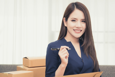 La donna graziosa di affari dell'ufficio sta preparando l'imballaggio di ordine per il cliente