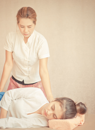 Thai Therapist is giving massage to the upper part of a woman