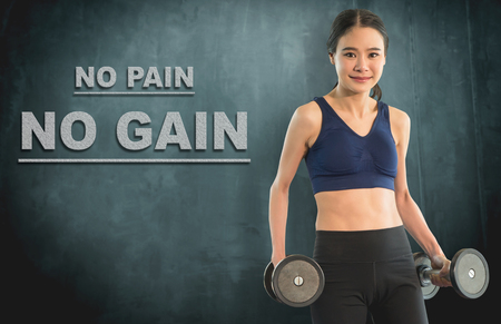 Slim work out woman with dumbbell for no pain no gain concept