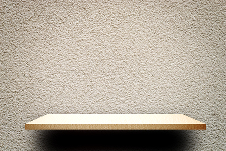Empty wooden shelf product display on Rough gray cement wall