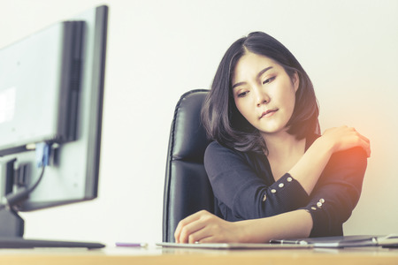 Female office worker is suffering injury on shoulder from long hour of work 스톡 콘텐츠