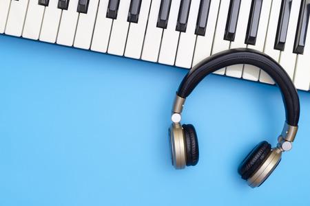 Muziekhoofdtelefoon en Muziektoetsenbord op blauwe exemplaarruimte Stockfoto - 94318887